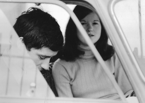 1970s Outdoor portrait of young couple in the countryside. Piandisco Arezzo, Tuscany Italy. Fiat 500. Black and white taken with 35mm film