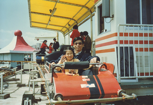 1990.5.1, CHINA, Beijing.  Father takes his daughter on a rollercoaster in the playground.