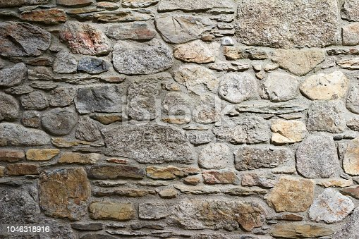 This abstract background image features a sunlit centuries old gray and brown color European stone wall with sparse growing and dried vegetation.