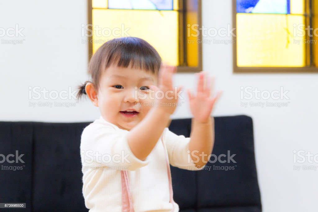 1-year-old girl dancing with expressive hand movements stock photo