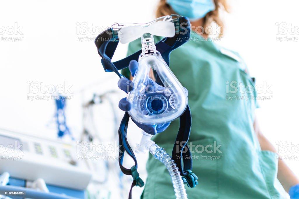 COVID19 / 2019-ncov concept: Verpleegkundige past een masker van de mechanische ventilatiemachine toe, die op de voorgrond te zien is. therapie die wordt gebruikt voor longademhaling, op de intensive care. - Royalty-free Ademhalingsbeschermingsmasker Stockfoto