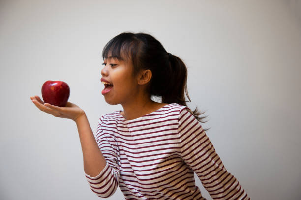 20s teenager filipino woman with red apple portrait on casual cloth background - philippines girl stock photos and pictures