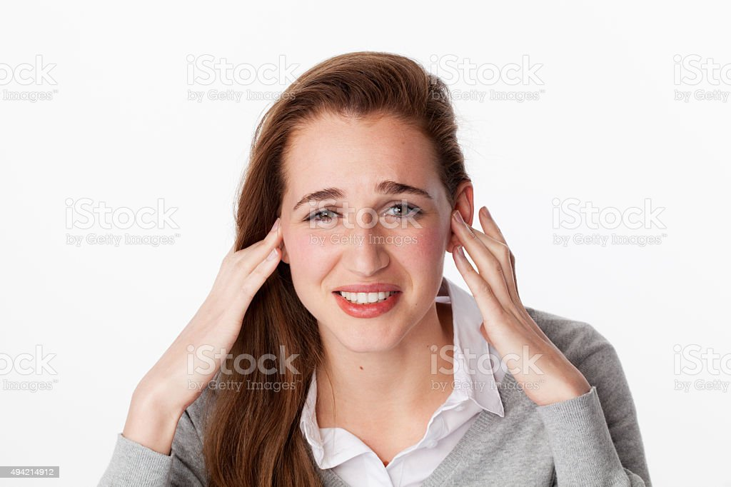 20s woman annoyed by noise or having jaw ache stock photo