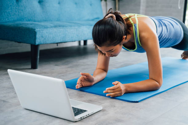 20s young Asian woman in sportswear doing plank poses while watching fitness training class on computer laptop online. Healthy girl exercising and learning in living room. Internet education concept