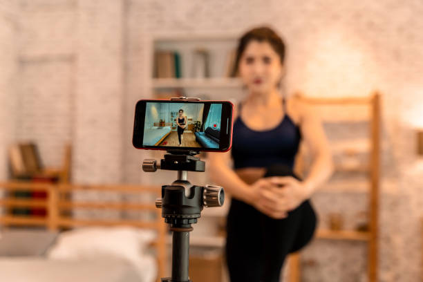 20s young Asian woman in sportswear doing talking to camera and explaining fitness tutorials online. Healthy girl blogger in living room at home. Teaching online bodybuilding class concept stock photo
