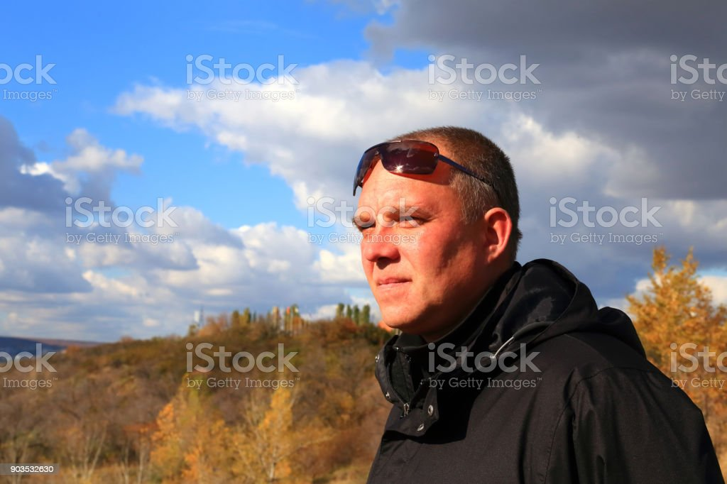 A 35-40-year-old tourist in a black jacket and sunglasses looks thoughtfully into the distance against the background of the landscape. stock photo