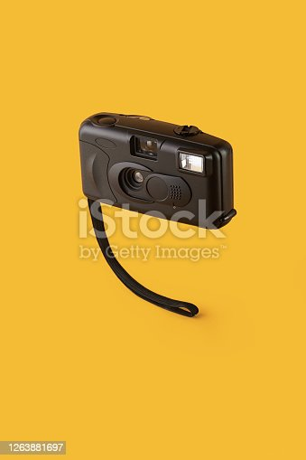 istock 35mm point and shoot film camera levitating on yellow / orange colored background 1263881697