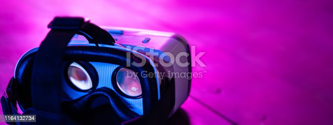 istock VR 3d 360 headset glasses goggles in futuristic purple neon light on table desk, virtual augmented ar reality innovative experience digital technology background concept, copy space wide photo banner 1164132734
