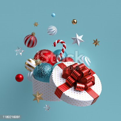 istock 3d Christmas ornaments and glass balls falling out of open round box, white wrapped gift with red bow. Winter holiday package. Levitating objects. Festive clip art isolated on blue background 1180216091