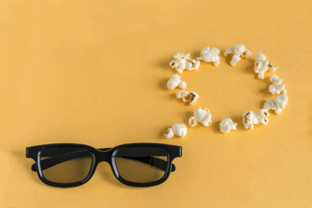 3d glasses and a think/speech bubble of popcorn on a yellow background. stock photo