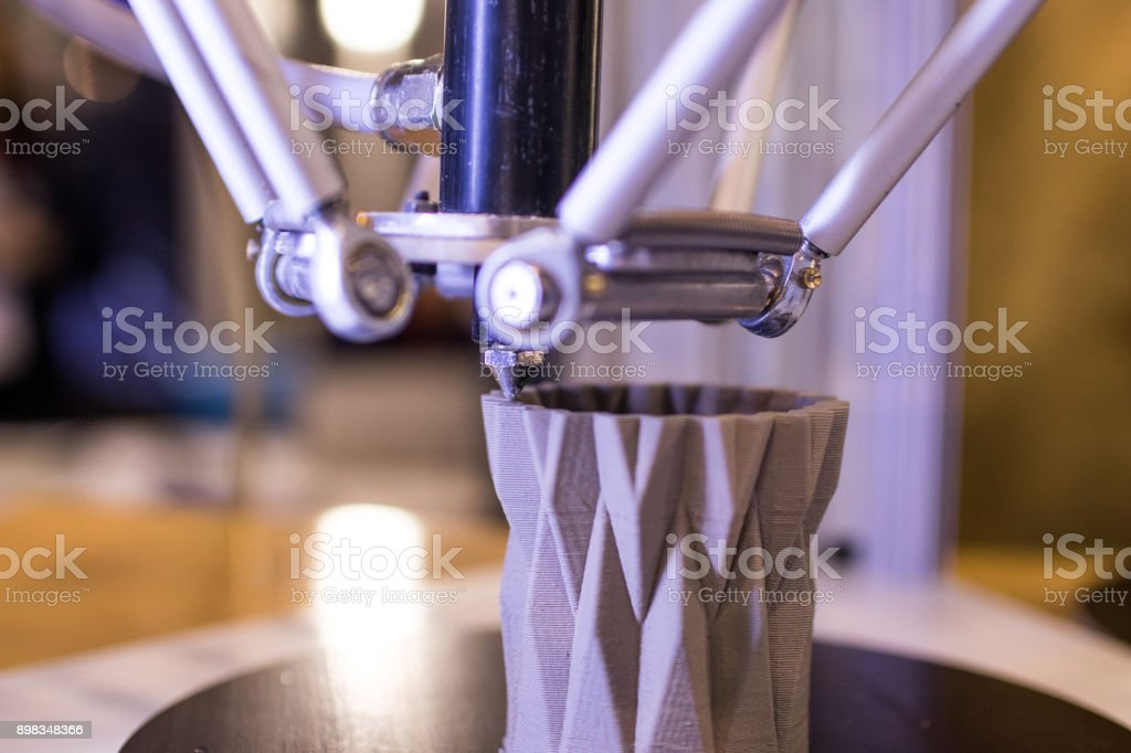 3d printer in the process of making a geometric vase stock photo