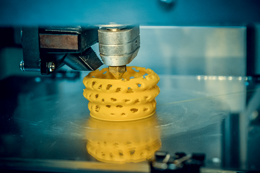 istock 3d printer printing objects yellow form closeup 1001753964