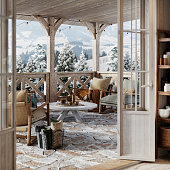 Beautiful snowy winter cottage balcony with wooden center table, armchairs and coffee cups.