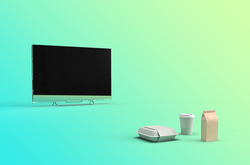 istock 3d render of a smart television with take out lunch food packet, coffee mug and paper coffee bag blank mockup. leisure concept illustration. 1210811332