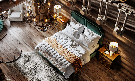 High angle shot of a double bed in winter cottage. Luxurious bedroom in modern style log house.