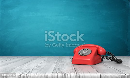 istock 3d rendering of a bright red dial phone standing on a wooden desk and a blue wall background 836401440
