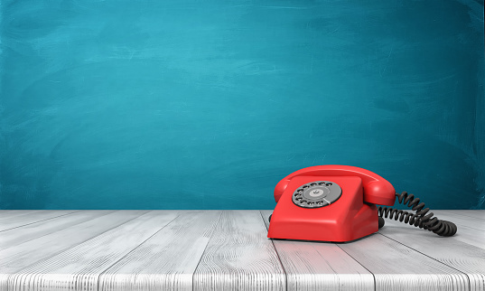 3d rendering of a bright red dial phone standing on a wooden desk and a blue wall background