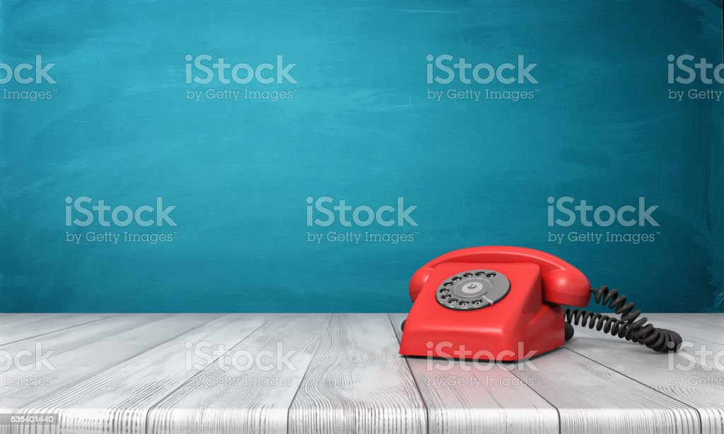 3d rendering of a bright red dial phone standing on a wooden desk and a blue wall background stock photo