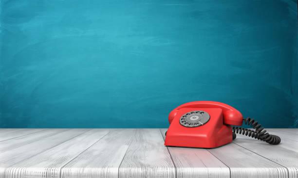 3d rendering von einem leuchtend roten wählen sie telefon stehend auf einem schreibtisch aus holz und eine blaue wand-hintergrund - nostalgie telefon stock-fotos und bilder