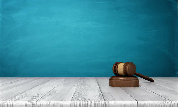 3d rendering of a brown wooden judge gavel and sound block lying on a wooden table against blue background stock photo