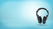 3d rendering of a large black wireless padded headphones in front view on blue background