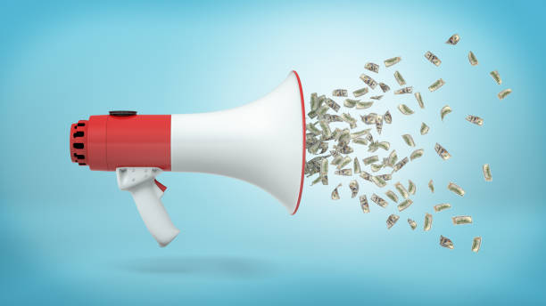 3d rendering of a large red and white megaphone in a side view with many dollar bills flying out of it on a blue background. – zdjęcie