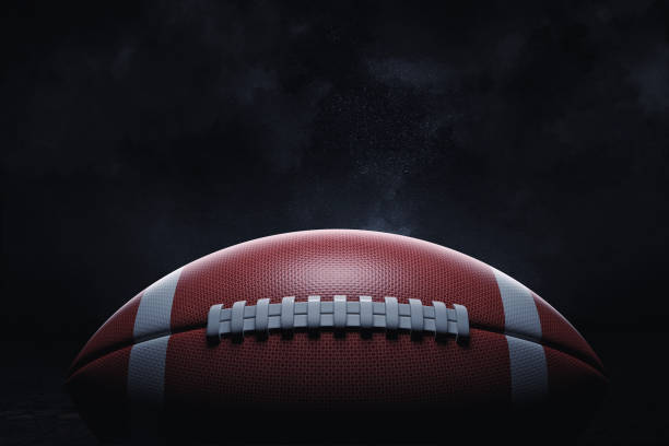 3d rendering of a leather ball for american football lying with its seams in focus on a dark background. - football zdjęcia i obrazy z banku zdjęć