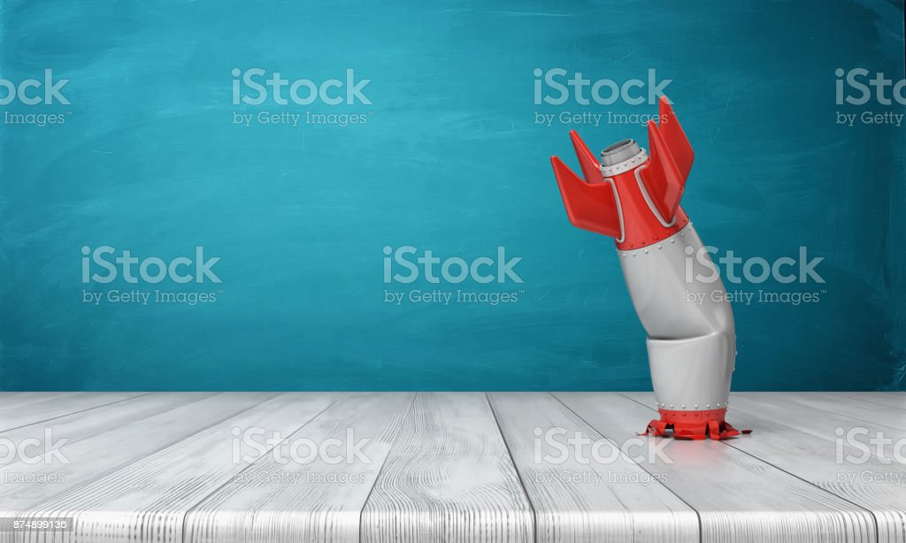 3d rendering of a red and silver realistic model of a retro rocket stands crashed into a wooden desk on a blue background. stock photo
