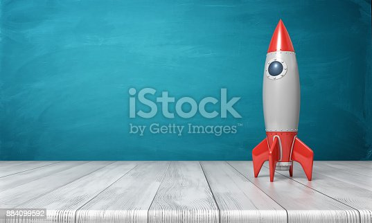 istock 3d rendering of a red and silver realistic model of a retro rocket stands on a wooden desk on a blue background 884099592