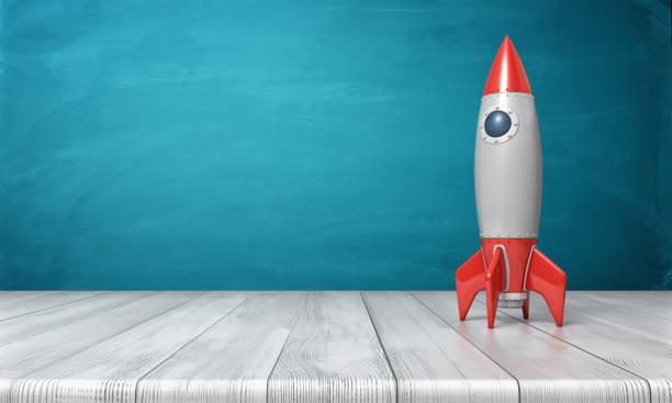 3d rendering of a red and silver realistic model of a retro rocket stands on a wooden desk on a blue background stock photo