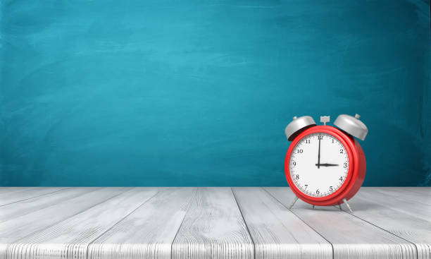 3d rendering of a red vintage alarm clock with metal bells stands on a wooden desk in front of blue background - clock stock pictures, royalty-free photos & images