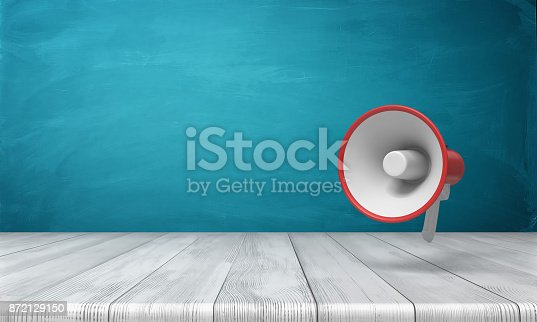 istock 3d rendering of a single red and white megaphone hanging vertically above a wooden desk. 872129150