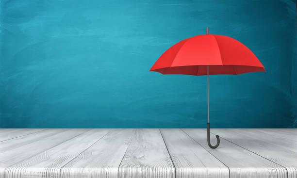 Render 3D de un solo paraguas clásico rojo con un pie de dosel abierto encima de un escritorio de madera sobre fondo azul - foto de stock