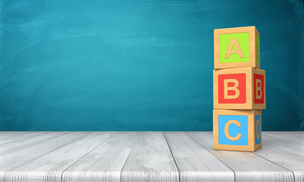 3d rendering of a three toy blocks standing on a wooden desk in one tower with letters A, B and C on them. stock photo