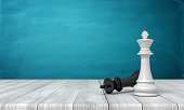 istock 3d rendering of a white chess king standing near a fallen black king on a wooden desk background. 1171920105