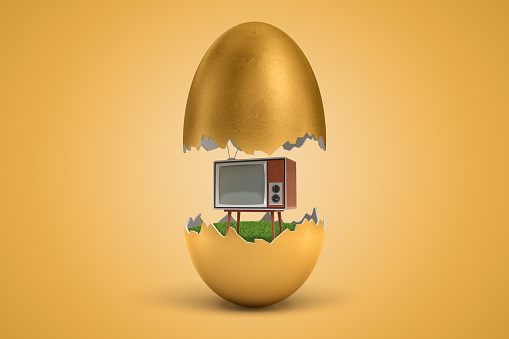istock 3d rendering of gold egg cracked in two, upper half levitating in air, retro TV set standing on green grass inside lower half, on ocher background. 1179971454