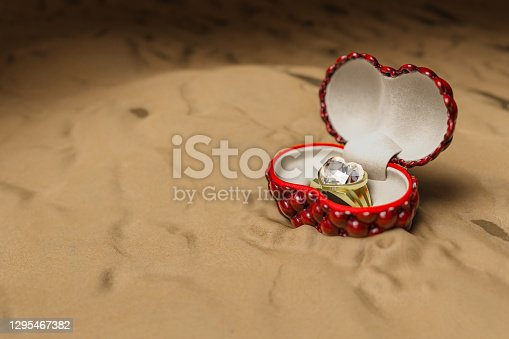 istock 3d rendering of the heart shape diamond ring in a red box on a night sand beach background. 1295467382