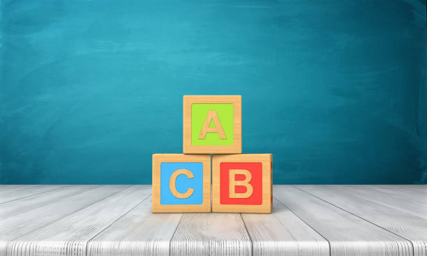 3d rendering of three toy blocks of different colors with letters a, b and c on them standing on a wooden desk. - alphabetical order stock pictures, royalty-free photos & images