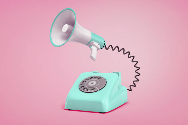3d rendering of turquoise retro phone with a dial stands on a pink background connected to a megaphone by a black cord. stock photo