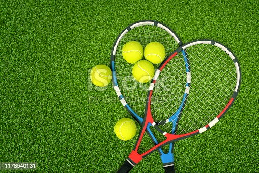 3d rendering of two tennis rackets and yellow tennis balls on green grass background. Games and sports. Outdoor activities. Sporting goods.