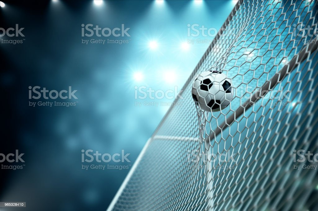 3d rendering soccer ball in goal. Soccer ball in net with spotlight and stadium light background, Success concept. Soccer ball on blue background. royalty-free stock photo