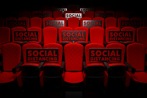 3d rendering the row of red cinema seats in the empty theater auditorium with the banner social distancing for against pandemics of COVID-19 concept.