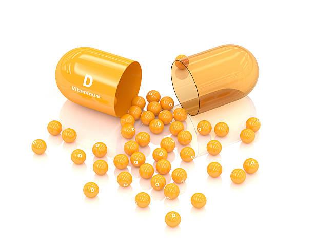 3d rendering vitamin d capsule lying on white - vitamin d stok fotoğraflar ve resimler