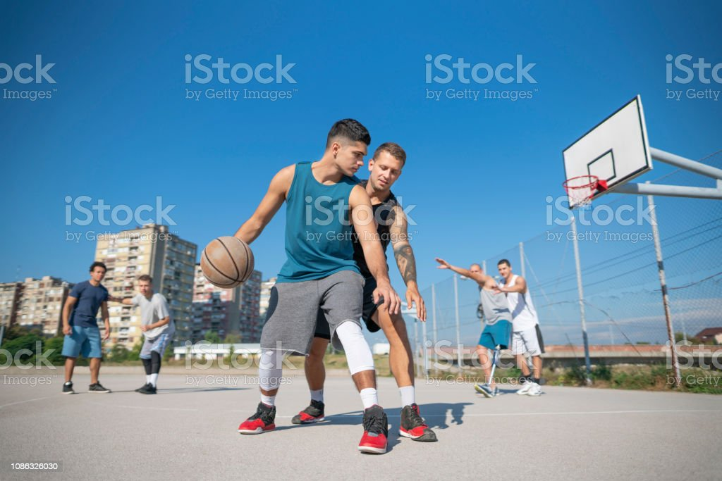 Group of friends playing street basketball in their neighborhood.
