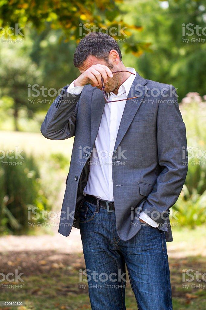 40s gray hair businessman having pollen allergies outdoors stock photo