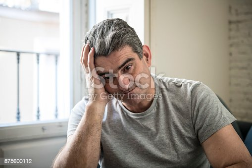 istock 40s or 50s sad and worried man with grey hair sitting at home couch looking depressed and wasted in sadness face expression in depression and life problems concept 875600112