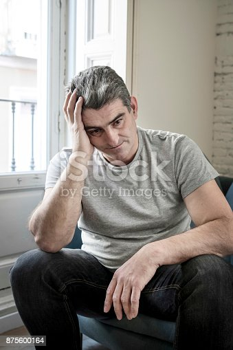 istock 40s or 50s sad and worried man with grey hair sitting at home couch looking depressed and wasted in sadness face expression in depression and life problems concept 875600164