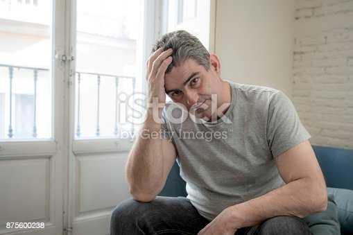 istock 40s or 50s sad and worried man with grey hair sitting at home couch looking depressed and wasted in sadness face expression in depression and life problems concept 875600238