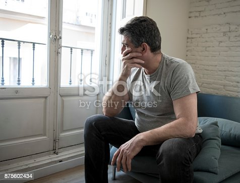 istock 40s or 50s sad and worried man with grey hair sitting at home couch looking depressed and wasted in sadness face expression in depression and life problems concept 875602434