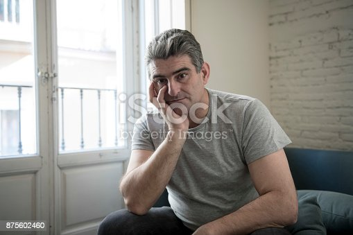 istock 40s or 50s sad and worried man with grey hair sitting at home couch looking depressed and wasted in sadness face expression in depression and life problems concept 875602460